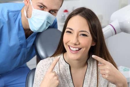 Tevreden tandartspatiënt die haar perfecte glimlach in een overleg toont