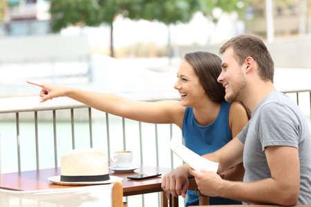 Couple ot tourists pointing locations sitting in a coffee shop