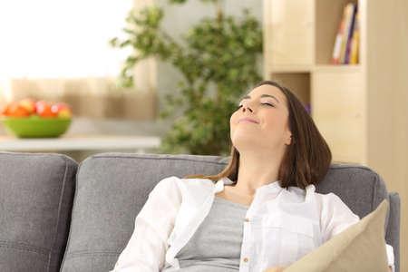 Portrait d'une femme satisfaite relaxant allongé sur un canapé chez soi Banque d'images - 84974571