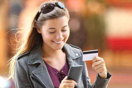 Portrait of a happy shopper buying on line with a smart phone and credit card on the street