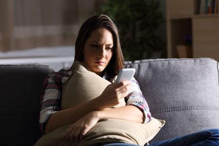 슬픈 소녀 베개를 들고 집에서 소파에 앉아 어둠 속에서 전화 메시지를 읽고