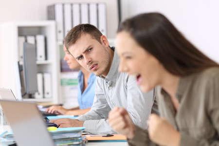 사무실에서 성공적인 동료를보고 질투하는 직원의 초상화 스톡 콘텐츠