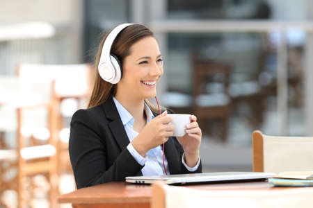positivismo: Single executive listening audio content and holding a cup sitting in a coffee shop