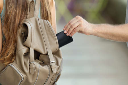 Close up of a thief hand stealing a phone from a bag on the street Stock Photo