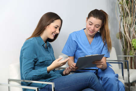 Nurse explaining medical procedure to a patient in a waiting room Stockfoto
