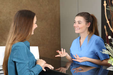 Happy dentist or nurse attending a patient in a consultation