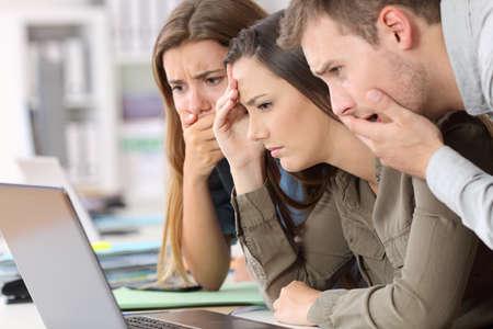 Tres empleados preocupados leyendo malas noticias en línea en una computadora portátil en la oficina Foto de archivo - 84651475