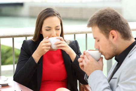 positivismo: Two happy executives drinking coffee cups sitting in a bar terrace