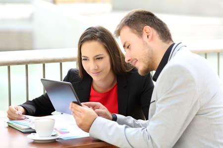 Zwei Führungskräfte beraten auf Linie Inhalt mit einer Tablette sitzen in einem Café Standard-Bild - 84651455