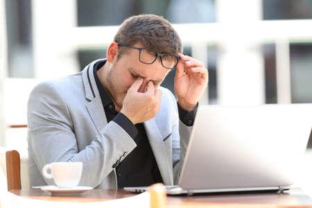 エグゼクティブ苦しみ眼精疲労コーヒー ショップに座ってラインで作業に疲れて