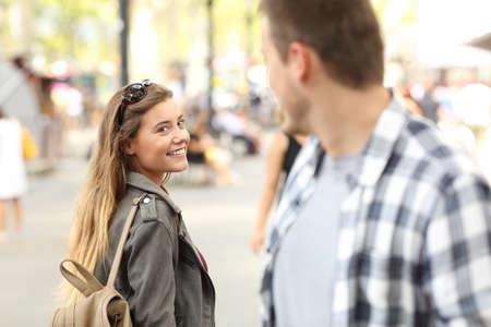 Nieznajomi dziewczyny i facet flirtują patrząc sobie nawzajem na ulicę