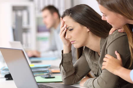 Droevige medewerker die slecht nieuws ontvangt, wordt getroost door een collega op kantoor Stockfoto