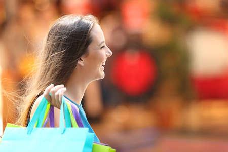 Seitenansicht Porträt einer glücklichen Shopper Shopping zu Fuß auf der Straße