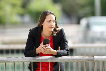 Pensive executive holding a mobile phone leaning in a railing outdoors