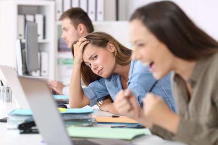 Trabajador preocupado junto a uno exitoso que está entusiasmado leyendo buenas noticias en línea en la oficina