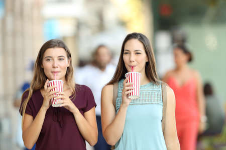 Front view portrait of two friends drinking a takeaway refreshment in the street
