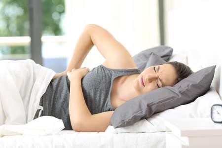 Mujer acostada en una cama despertando dolor de espalda en su casa o habitación de hotel Foto de archivo - 85485841