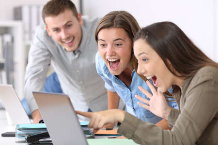 Three excited employees receiving good news on line at office Foto de archivo