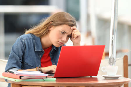 Single frustrated student trying to understand on line tutorials in a laptop sitting in a restaurant
