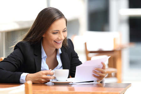 Single happy businesswoman reading a letter sitting in a coffee shop Stockfoto