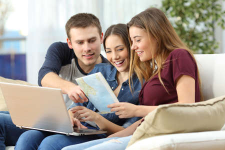 Three happy friends planning a travel on line and consulting a guide sitting on a sofa at home Imagens