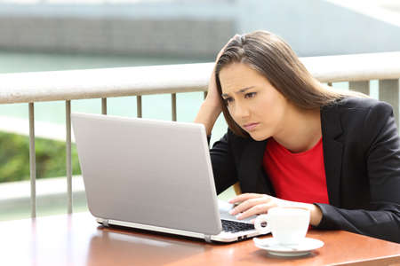 Single sad executive woman reading bad news on line in a laptop sitting in a coffee shop Stock Photo
