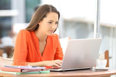 Studente universitario serio serio in arancione che utilizza un computer portatile che si siede in un negozio di caffè Archivio Fotografico