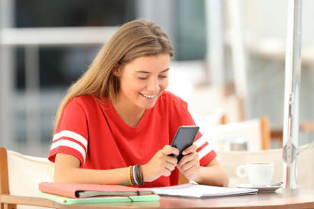 Happy student in red using a smart phone sitting in a restaurant Stock Photo