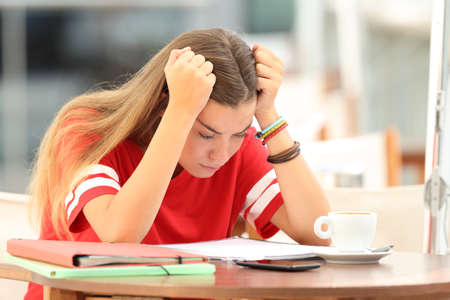 Single frustrated student girl trying to understand notes sitting in a bar