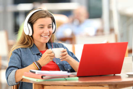 Single relaxed student watching media content in a red laptop sitting in a restaurant