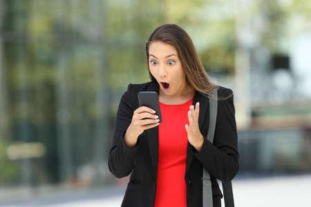 Ejecutivo asombrado solo para encontrar noticias increíbles en línea en un teléfono inteligente en la calle Foto de archivo
