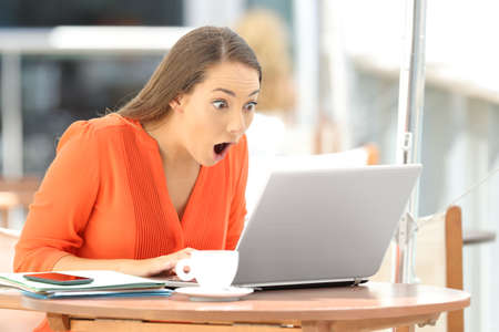 Single astonished student finding amazing content on line in a laptop sitting in a restaurant
