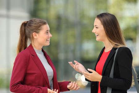 Vista laterale di due dirigenti felici che parlano sulla strada