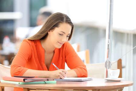 Étudiant universitaire célibataire prenant des notes assis dans un café