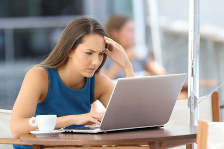 Nico preocupado lectura ejecutiva en línea de contenido en un ordenador portátil sentado en un bar al aire libre Foto de archivo - 85245067