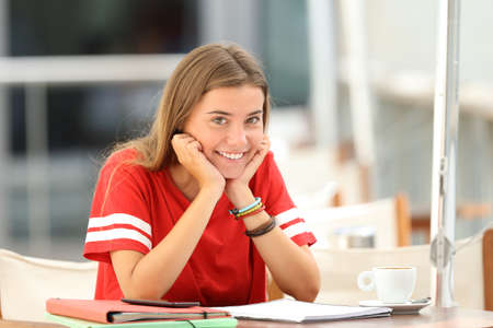 Happy student posing alone and looking at you sitting in a coffee shop