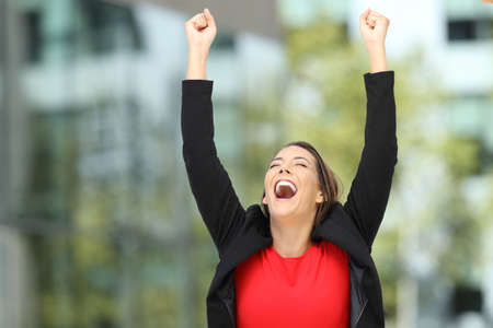 Single excited executive raising arms na succes op de straat Stockfoto - 85339573