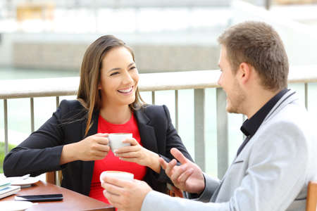 Two happy executives talking during a coffee break sitting in a bar Stockfoto
