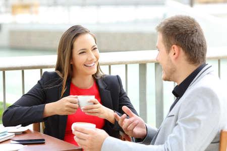 Zwei glückliche Führungskräfte reden während einer Kaffeepause in einer Bar sitzen Standard-Bild - 85339574
