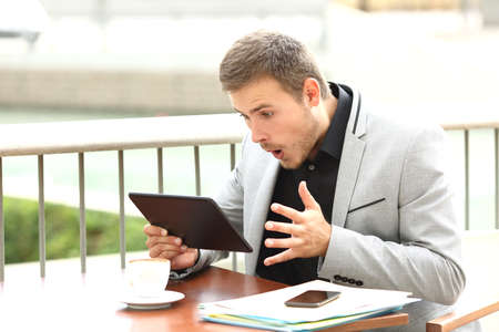 Single amazed executive male reading surprising news in a tablet sitting in a coffee shop
