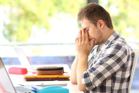 Zijaanzicht van een vermoeide student alleen in een klaslokaal