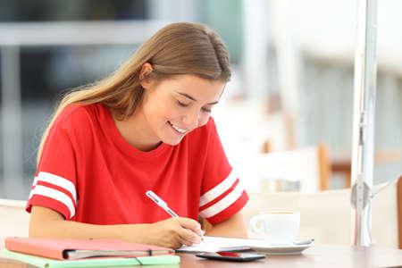 Studentessa felice studente prendere appunti seduti in un negozio di caffè Archivio Fotografico - 85272189
