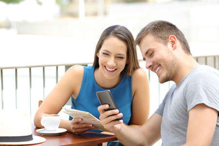generic location: Couple of tourists searching on line locations in a smart phone and guide during travel sitting in a coffee shop Stock Photo