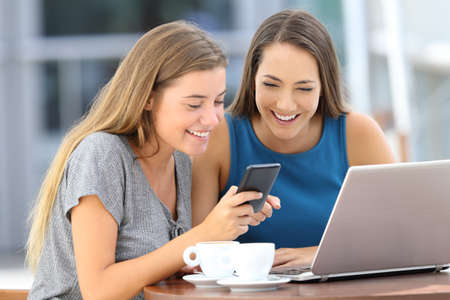 Two funny friends sharing a smart phone watching media content on line sitting in a coffee shop