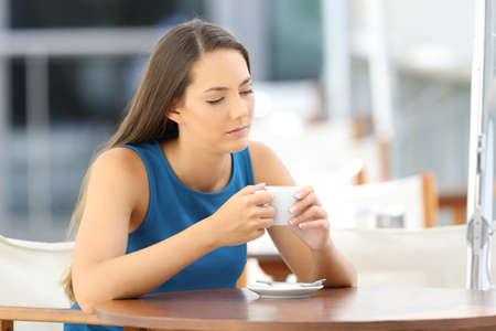 Single pensive and sad lady sitting in a coffee shop terrace Stock Photo