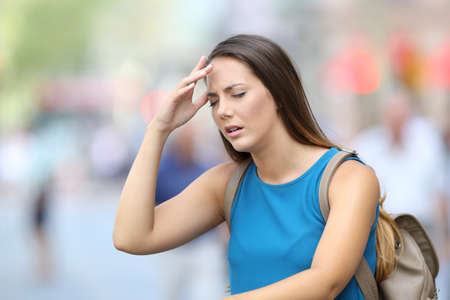 Single woman suffering headache outdoors in the street Stok Fotoğraf