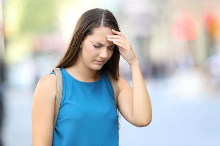 거리에서 걷고있는 두통을 앓고있는 한 여자