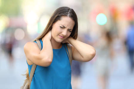 Single woman suffering neck ache walking on the street