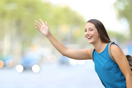 Single happy woman hailing taxi cab on the street Standard-Bild