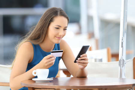 Single shopper buying on line with a phone and credit card sitting in a restaurant terrace